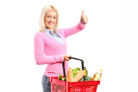 Girl holding a shopping basket full of groceries and giving a thumb up isolated on white background photo