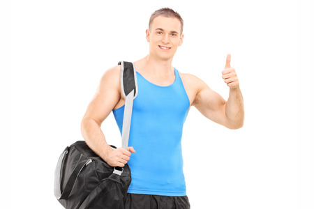 posing  agree: Male athlete giving thumb up isolated against white background