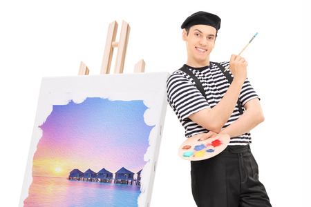 Male artist standing by a painting on an easel isolated against white background
