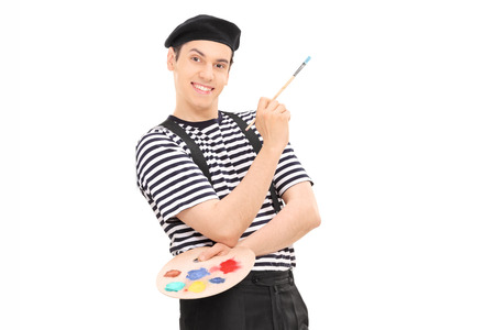 Male painter holding a paintbrush and leaning against a wall isolated against white background
