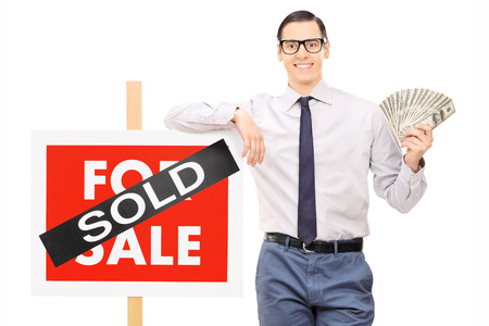 Male realtor holding money next to a sold sign isolated against white background photo