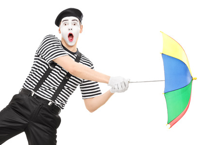 simulating: Mime artist holding an umbrella simulating being blown by wind isolated on white background Stock Photo