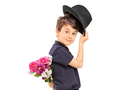 Profile shot of a cute little boy holding flowers behind his back isolated against white background photo