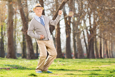 man looking at sky: Senior man playing air guitar in the park