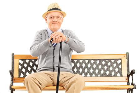 hombre sentado: Caballero mayor con un bastón sentado en el banco aislado en el fondo blanco Foto de archivo