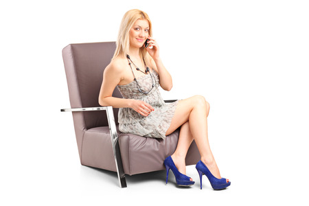 seated: Woman talking on phone seated in an armchair isolated on white background Stock Photo