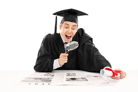 job searching: College graduate searching for job in newspaper isolated on white background