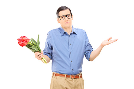 stood up: Displeased young man holding a bunch of flowers isolated on white background