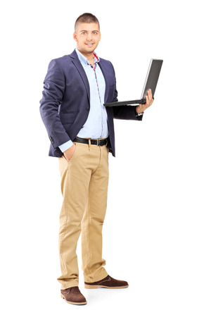 Full length portrait of a man holding a laptop isolated on white background photo