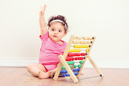 abaco: Bebé que se sienta en el suelo y levantar la mano con un ábaco a su lado