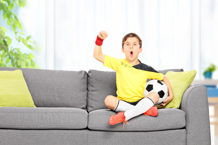 football jersey: Little boy watching a football match seated on a sofa at home Stock Photo