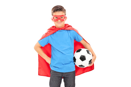 Boy in superhero costume holding a football isolated on white background photo