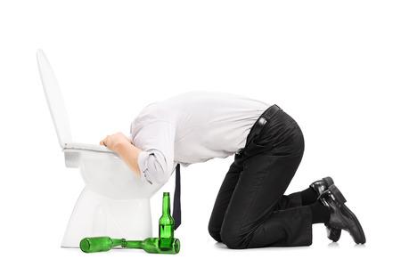 vomito: Hombre borracho vomitar en un retrete con botellas vacías de cerveza a su lado aislado en fondo blanco