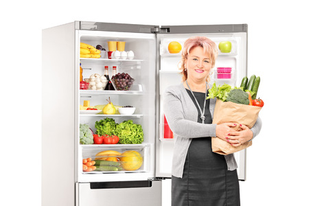 vertical fridge: Woman with bag of vegetables in front of a fridge isolated on white background Stock Photo