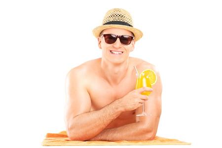 shirtless guy: Individuo descamisado que miente en la toalla y beber un c�ctel aislado sobre fondo blanco Foto de archivo