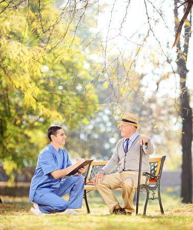 Doctor talking to senior gentleman in park shot with tilt and shift lens photo