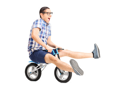 Carefree young guy riding a small bike isolated on white background Reklamní fotografie