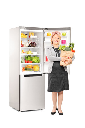 Full length portrait of a woman with bag of groceries in front of a fridge isolated on white background photo
