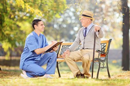 male nurse: Male nurse and an elderly having a conversation in park