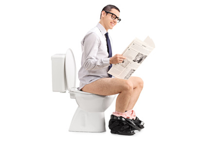 Man reading a newspaper seated on a toilet isolated on white background Archivio Fotografico