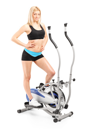 Active woman posing on a cross trainer machine isolated on white background photo