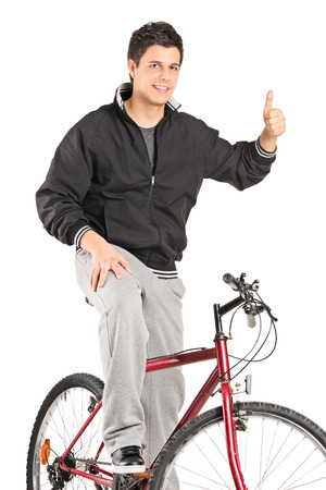 posing  agree: Vertical shot of a young man on a bike giving a thumb up isolated on white background Stock Photo