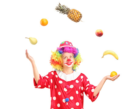 Female clown joggling a bunch of fruits isolated on white background photo