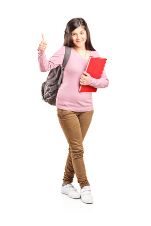 posing  agree: Full length portrait of a teenage schoolgirl giving a thumb up isolated on white background Stock Photo