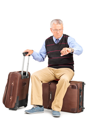 late sixties: Senior tourist checking the time seated on his luggage isolated on white background Stock Photo