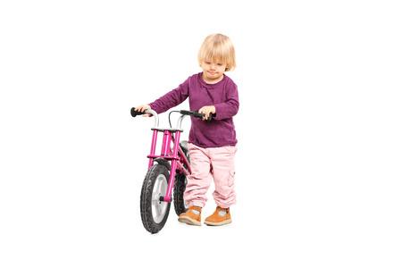 niño empujando: Niña empujando una bicicleta pequeña aislado en el fondo blanco