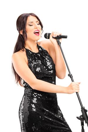 白い背景で隔離のマイクを歌うエレガントな女性歌手 写真素材