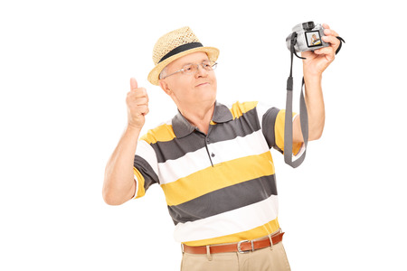 Senior gentleman taking a selfie with camera and giving thumb up isolated on white background photo