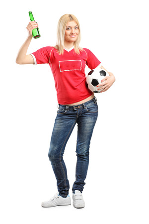 Full length portrait a young female fan holding a beer bottle and football isolated on white background photo
