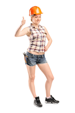 Full length portrait of a female construction worker giving thumb up isolated on white background photo