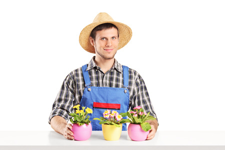 Male florist sitting on a table with many flower pots isolated on white background photo