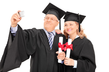Mature male and female in graduation gowns taking a selfie isolated on white background photo