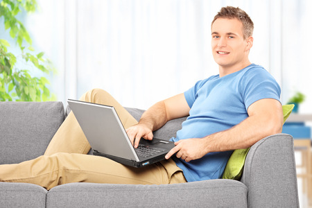 siting: Cheerful young man siting at home on a sofa with laptop