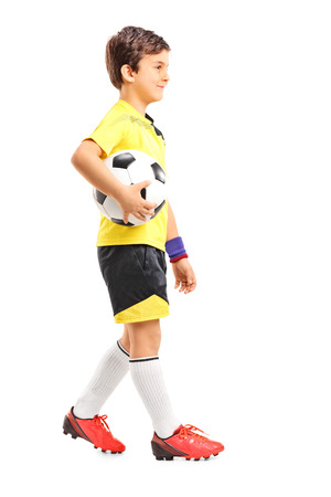 soccer boots: Profile shot of a young boy walking and holding a football isolated on white background Stock Photo