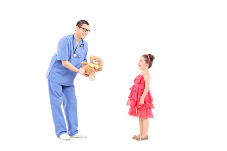 doctor giving glass: Doctor giving a teddy bear to a surprised little girl isolated on white background Stock Photo