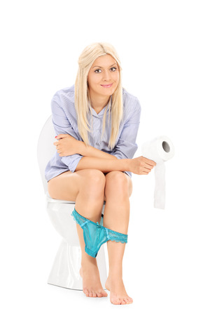 Young girl sitting on a toilet and holding toilet paper isolated on white background photo