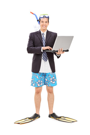 Full length portrait of a businessman with diving equipment holding laptop isolated on white background photo