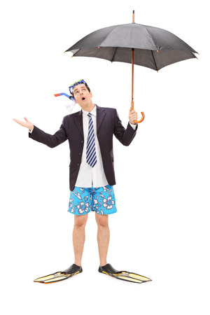 Full length portrait of a businessman with diving mask holding an umbrella isolated on white background photo
