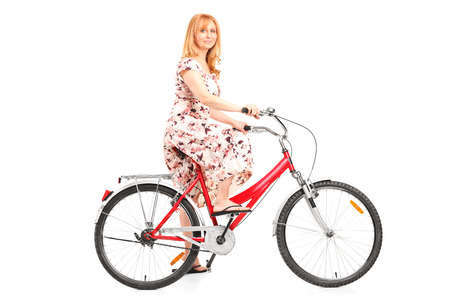 Mature woman riding a bike isolated on white background photo