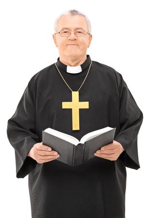 Felice sacerdote matura in possesso di una bibbia santa isolato su sfondo bianco