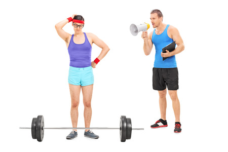 motivating: Coach motivating a nerdy guy to exercise, with a megaphone isolated on white background