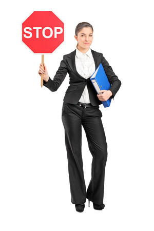 Full length portrait of a businesswoman holding a stop sign isolated on white background photo