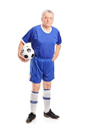 Full length portrait of a mature man in sportswear holding a football isolated on white background