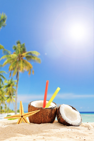 coconut drink: Creative cocktail in a coconut cup on a tropical beach on a hot summer day