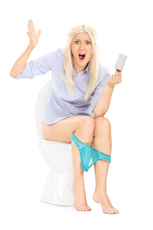 roll: Angry girl sitting on toilet and holding an empty toilet paper roll isolated on white background