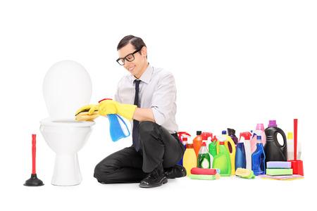 productos limpieza: Hombre sentado con un aseo con mont�n de productos de limpieza detr�s de �l aisladas sobre fondo blanco Foto de archivo
